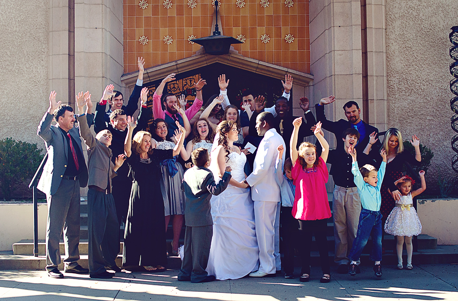 Joanna and her husband on their wedding day, surrounded by family.